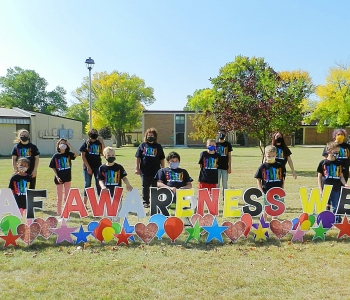 Students behind Deaf Awareness Week yard lettering